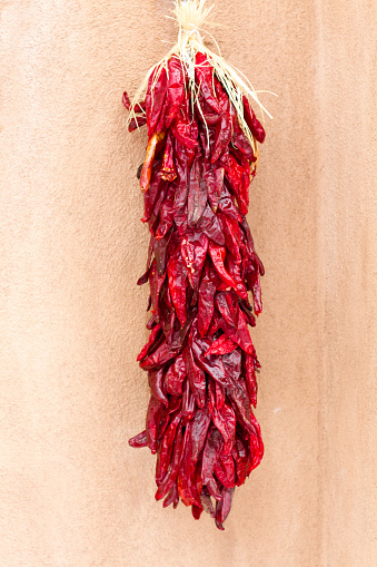 Red chile ristra with stucco wall in background